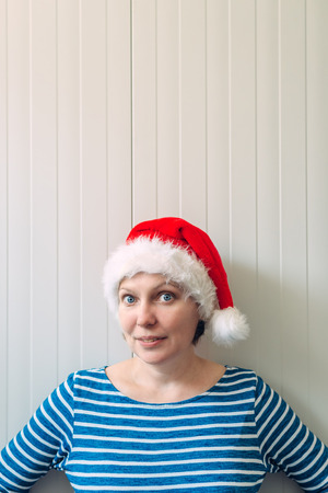 adult wall: Portrait of cheerful beautiful adult caucasian woman with Santa Claus hat against white plastic wall as copy space Stock Photo