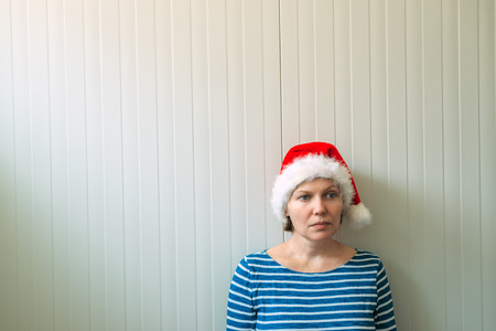 soledad: Disappointed woman with Christmas Santa Claus hat suffering from holiday depression, sad and lonely woman waiting New Year all let down