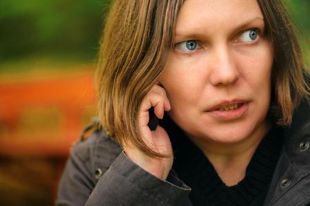 mujer pensativa: Mujer con expresión seria hablando por teléfono móvil en el parque, luz dramática viene a través de copas de los árboles y cayendo en su cara