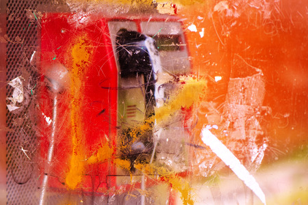 Demolished and vandalized public phone booth on street with graffiti spray marks and stains, selective focus