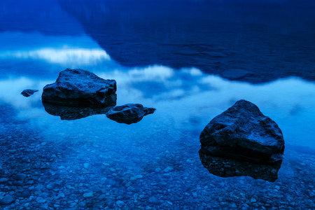 bohinj: Rocks in shallow lake water in the evening, tranquil idyllic scene of beauty in nature Stock Photo
