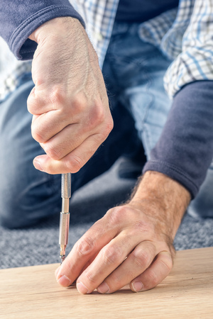 Man assembling furniture at home on the floor, hand with screwdriver Stock Photo