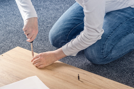 woman closet: Woman assembling furniture at home on the floor, hand with screwdriver Stock Photo