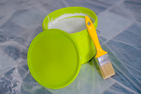 redecoration: Yellow paint brush and green bucket on the floor, ready for housework project and walls redecoration