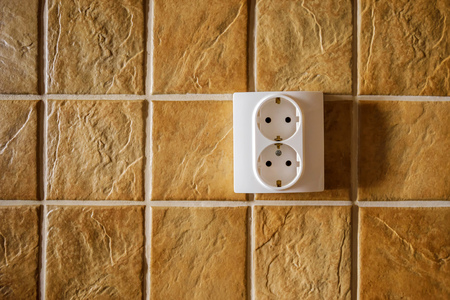 electric socket: White electric socket on kitchen wall with ceramic tiles pattern texture