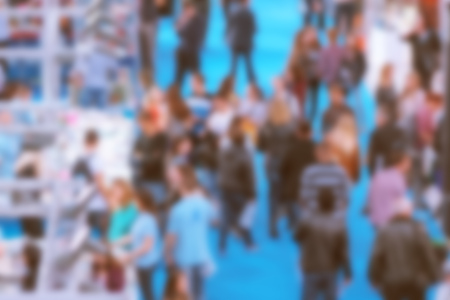 happening: Abstract blurred people attending event in exhibition hall, press conference or celebration party, visitors of indoor fair or other commercial happening, retro toned image. Stock Photo