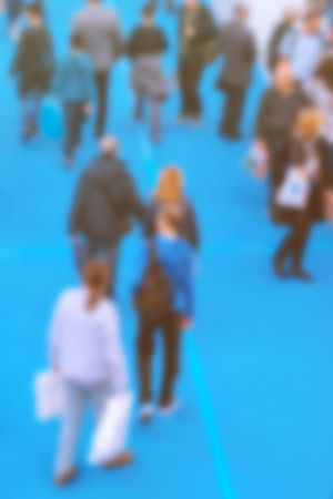 blurred people: Abstract blurred people attending event in exhibition hall, press conference or celebration party, visitors of indoor fair or other commercial happening, retro toned image. Stock Photo
