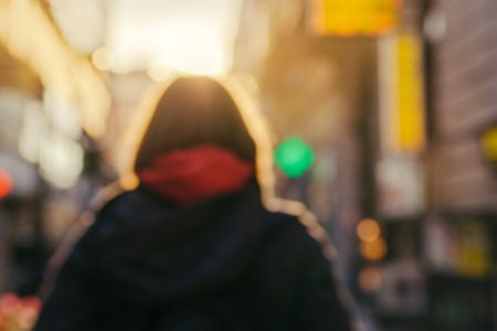 Blur image of unrecognizable female person from behind on the street in cold autumn afternoon Stock Photo