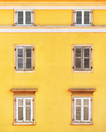 old building facade: Building facade and old windows with classic wooden venetian shutters blinds, mediterranean europe architecture vintage style