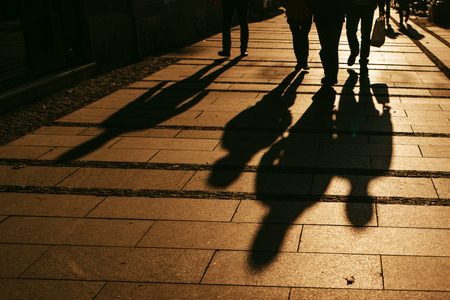 Silhouettes of people walking on city street and casting shadows on pavement, general public concept for any community related theme.