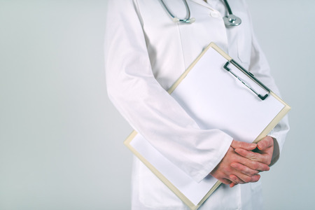 Female doctor in white uniform posing with blank clipboard pad as copy space for text or patients medical history. Woman as health specialist in medical exam, er, disease prevention, visit check or healthcare lifestyle concept