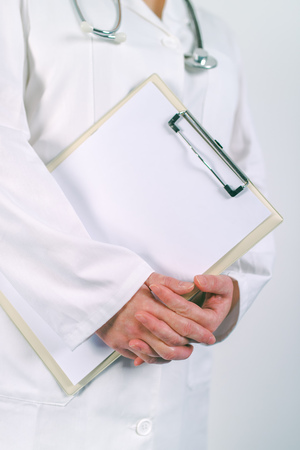 er: Female doctor in white uniform posing with blank clipboard pad as copy space for text or patients medical history. Woman as health specialist in medical exam, er, disease prevention, visit check or healthcare lifestyle concept