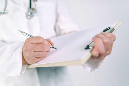 Female doctor in white uniform writing on clipboard paper patients medical history or medicine prescription. Woman as health specialist in exam, er, disease prevention, visit check or healthcare lifestyle concept