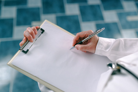 disease prevention: Female doctor in white uniform writing on clipboard paper patients medical history. Woman as health specialist in exam, er, disease prevention, visit check or healthcare lifestyle concept Stock Photo