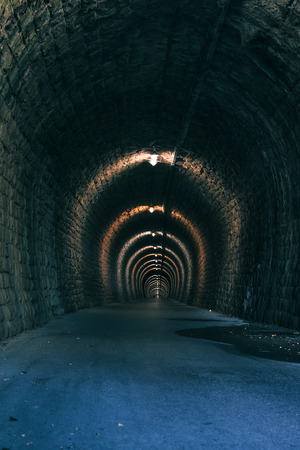 passageway: Old tunnel passageway with asphalt road for bikers and pedestrians Stock Photo