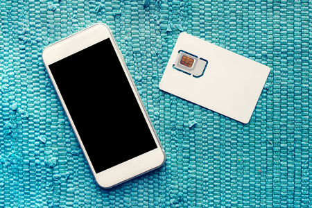 gsm: Smartphone with blank screen and mobile phone gsm SIM card on the table, top view