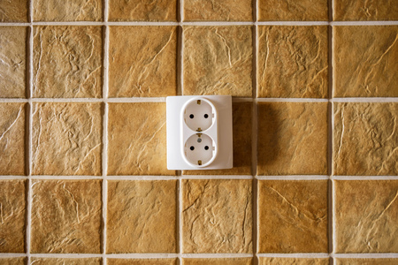 ceramic tiles: White electric socket on kitchen wall with ceramic tiles pattern texture