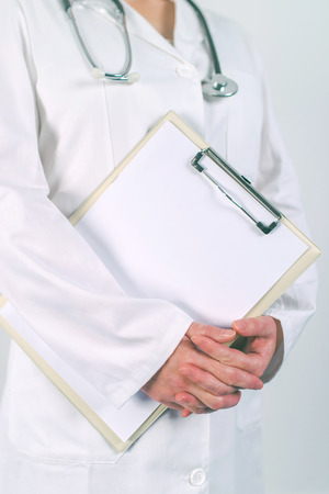 Female doctor in white uniform posing with blank clipboard pad as copy space for text or patients medical history. Woman as health specialist in medical exam, er, disease prevention or visit check. Stock Photo