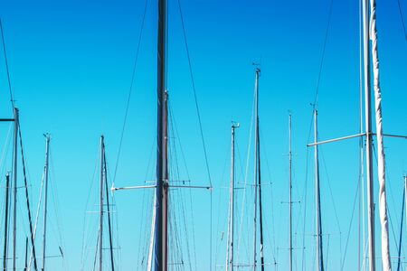 sailingboat: Sailboat masts in harbor against blue sky, summer holiday vacation abstract background