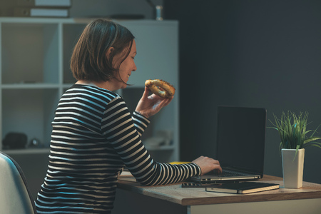 company person: Business woman eating baked snack over office laptop computer. Young adult caucasian female person is hungry while working overtime for the company.