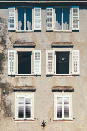 europe vintage: Weathered building facade and old windows with classic wooden venetian shutters blinds, mediterranean europe architecture vintage style Stock Photo