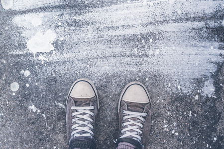 dry brush: Standing on concrete floor with white dry brush stains, male feet in worn sport shoes on the street Stock Photo
