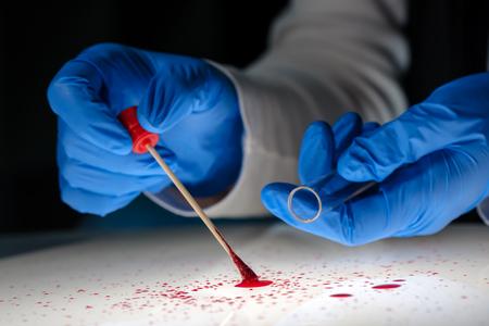 살인 범죄 현장에 면봉으로 혈액에서 DNA 샘플을 채취하는 법의학 기술자