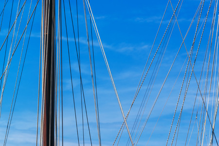 blue summer sky: Sailboat mast and ropes in harbor against blue sky, summer holiday vacation abstract background Stock Photo