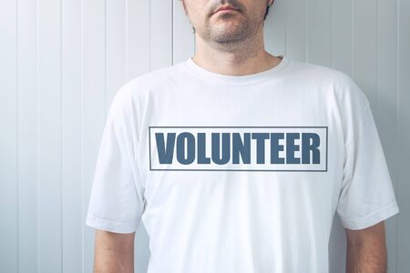 Guy wearing shirt with Volunteer label printed on chest, confident friendly person offering help