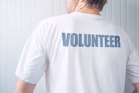 active adult community: Guy wearing shirt with Volunteer label printed on back, confident friendly person offering help