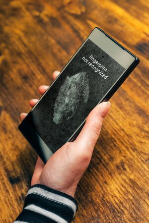 authenticate: Fingerprint not recognized message on mobile smartphone screen after a sensor scan of female thumb failed to authenticate user and unlock electronics device Stock Photo