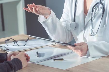 Vrouwelijke arts die patiënt in het ziekenhuisbureau adviseren tijdens regelmatig medisch examen, gezondheidszorg en preventieconcept. Stockfoto