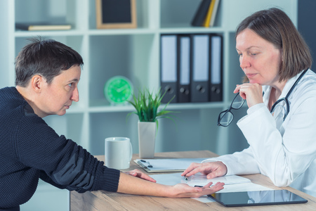 Female patient at orthopedic medical exam in doctors hospital office, traumatology and medical consultation for hand wrist injury Stock Photo