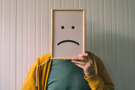 pessimist: Put a sad pessimistic face on, sadness and depressive emotions concept, man holding picture frame with smiley emoticon printed Stock Photo