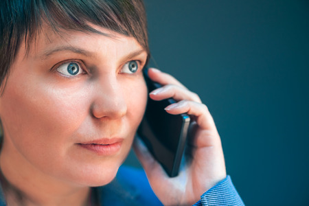 the caucasian beauty: Beautiful businesswoman talking on mobile phone, beauty portrait of young adult caucasian female having professional business conversation in office