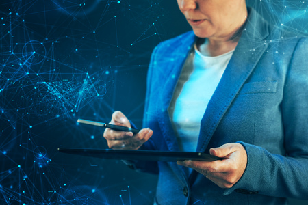 data synchronization: Smartphone and tablet data synchronization, businesswoman syncing files and documents on wireless electronic devices at business office Stock Photo