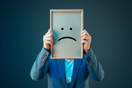 pessimist: Businesswoman is pessimistic about her future in corporate business, holding printed sad smiley emoticon over her face Stock Photo