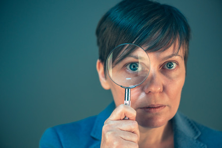 analyze: Beautiful businesswoman looking through magnifying glass - search, discover, explore, investigate and analyze concept.