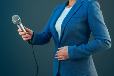 hand press: Elegant female journalist conducting business interview or press conference, hand with microphone