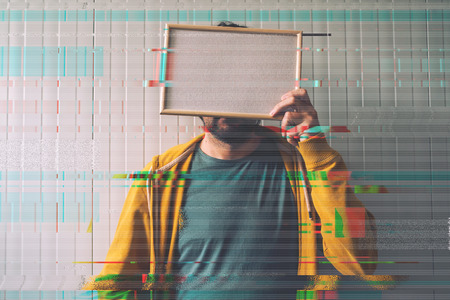 glitch: Unrecognizable man posing with blank picture frame over his face as copy space, digital glitch effect added in post production