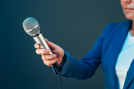 Elegant female journalist conducting business interview, hand with microphone