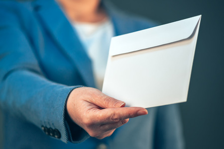 bribe: Businesswoman offering white envelope as bribe, concept of corruption in business activity