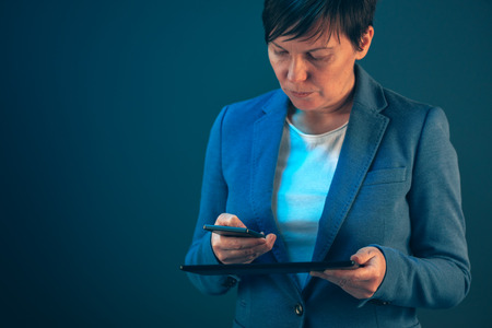 electronic tablet: Smartphone and tablet data synchronization, businesswoman syncing files and documents on wireless electronic devices at business office Stock Photo