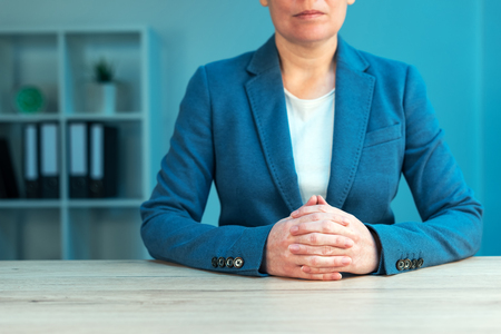 languages: Business negotiation skills with female executive sitting at office desk with confident pose and hands crossed, body language for determination and willpower Stock Photo