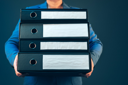 paperwork: Business woman holding document binders with archived paperwork and other corporate legal sheets, mock up copy space Stock Photo