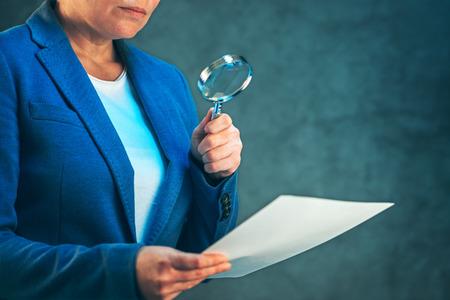 Vrouwelijke advocaat het lezen van juridische contract overeenkomst disclaimer met vergrootglas, de wettelijke vertegenwoordiger werkende onderneming Stockfoto