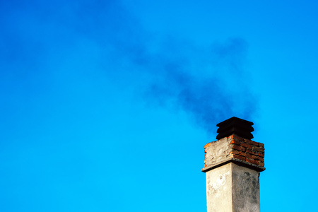 flue season: Smoke from house chimney on winter day Stock Photo