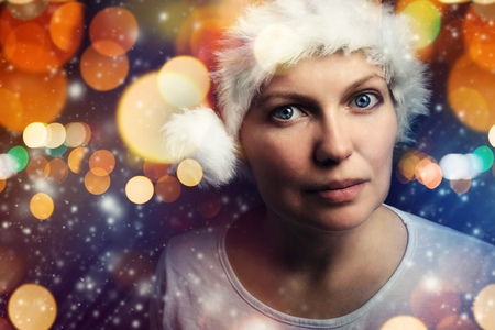 female christmas: Christmas female with Santa Claus hat beauty portrait with snowflakes and bokeh light effect Stock Photo