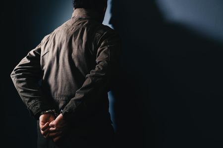 コピー スペースとして刑務所の壁に直面している手錠で男性犯罪者を逮捕