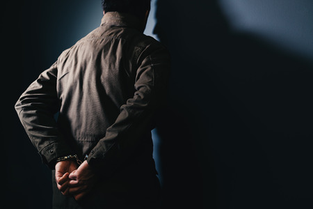 Arrested male criminal with handcuffs facing prison wall as copy space Banque d'images